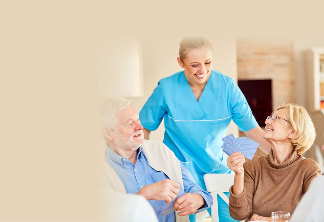 Smiling caregiver is watching at the card game of a senior citizen group in retirement home