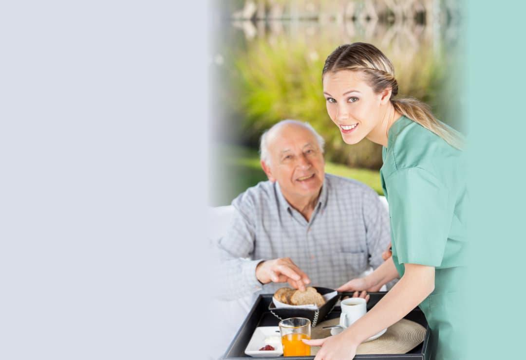 caregiver and elderly man smiling