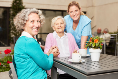 caregiver and senior woman holding her walking stick smiling