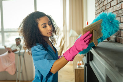 young nurse cleaning the apartment from dust while helping her patient