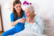 Kind doctor give water to elderly woman