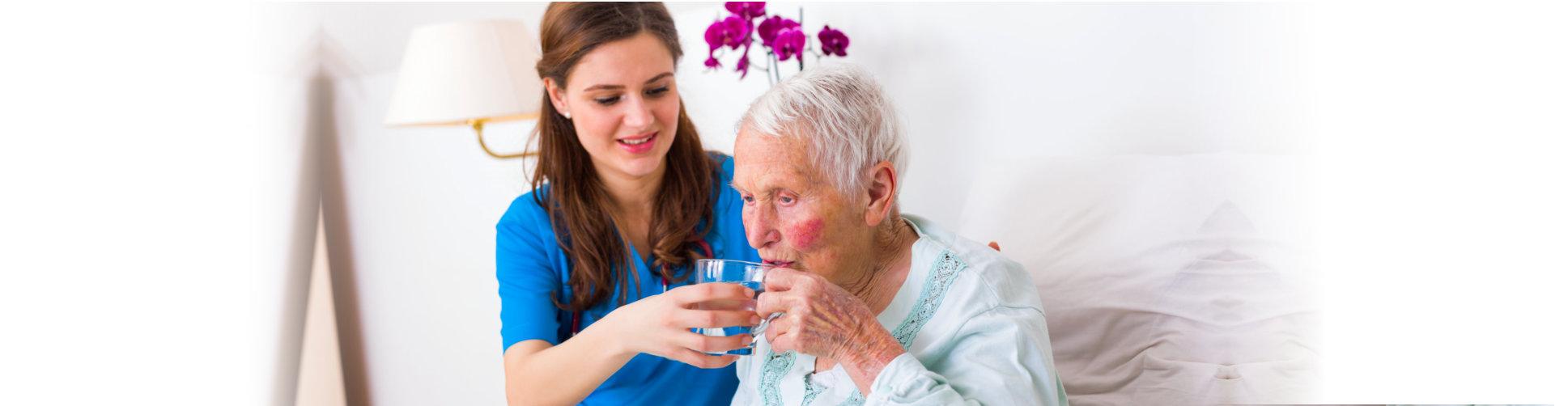 caregiver making the elder woman drink