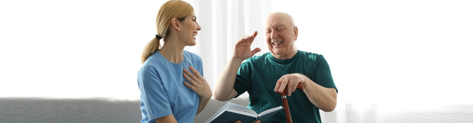 Nurse reading book to elderly man indoors. Assisting senior people
