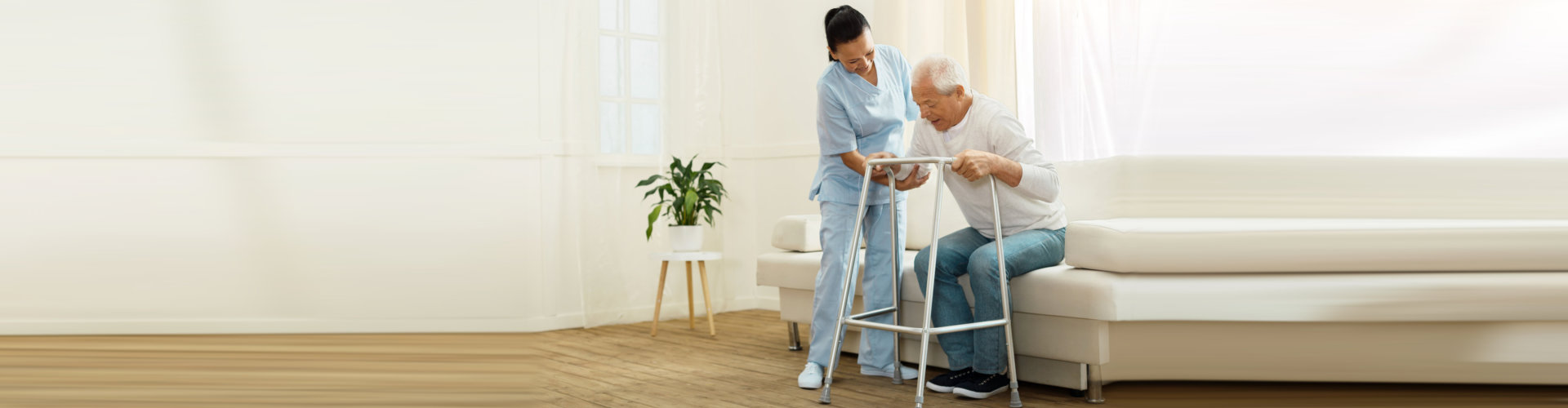 Delighted positive cheerful caregiver smiling and helping her patient to stand up while being near him