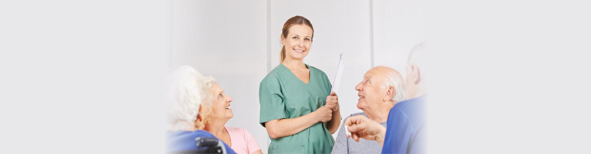 Smiling nurse between group of seniors in nursing home