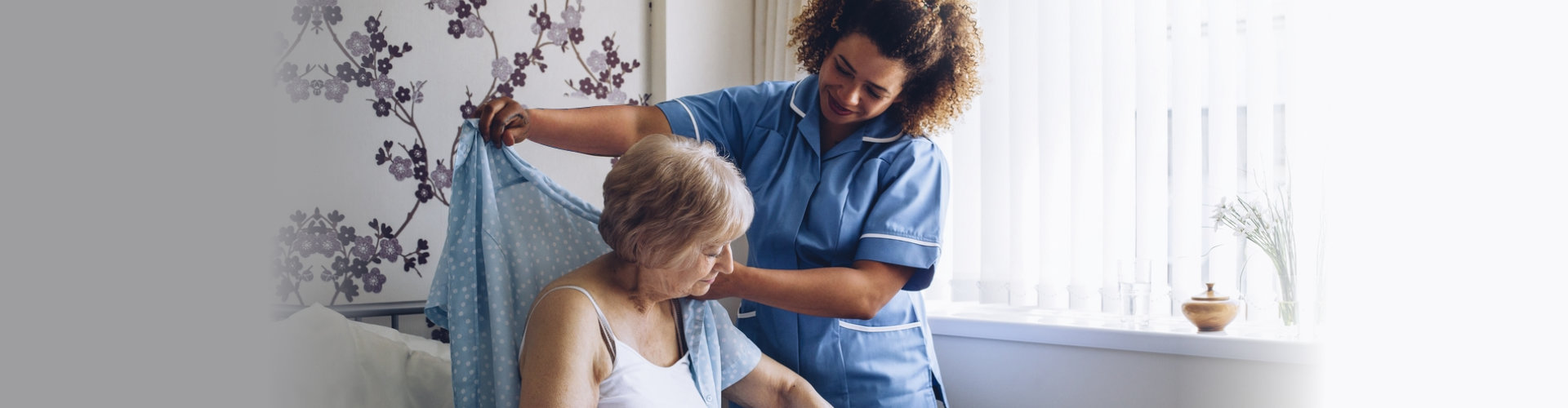caregiver assisting senior woman getting dressed in her bedroom